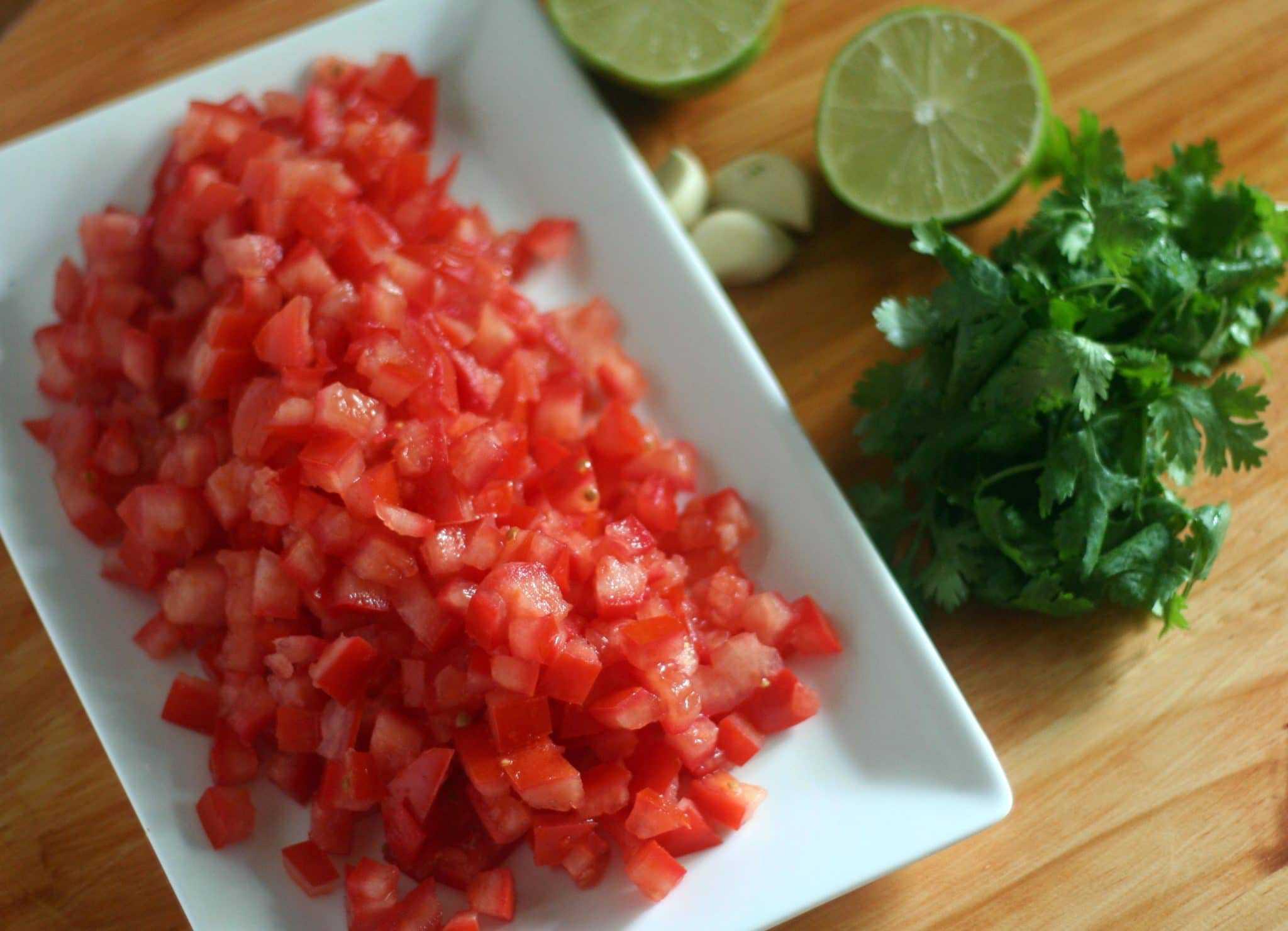 fresh tomatoes, limes, garlic, and fresh cilantro on a platter to make authentic pico de gallo