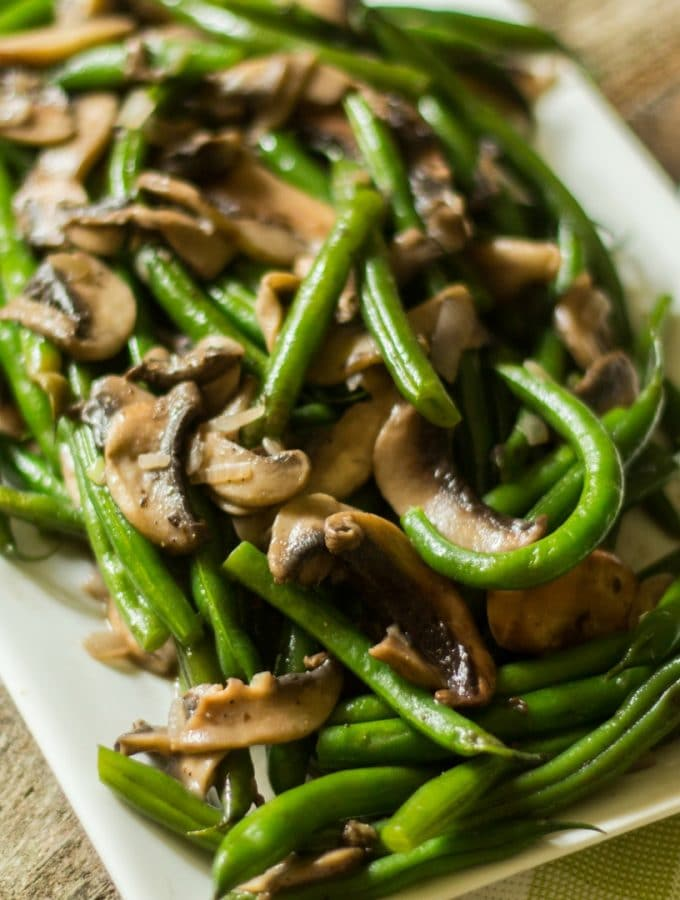 Green beans mushrooms with shallots on a white rectangular plate.