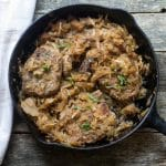 overhead photo of baked pork chops smothered with sauerkraut in a cast iron pan.