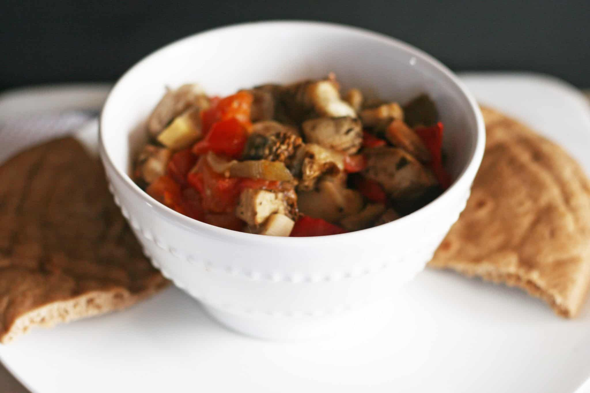 Slow Cooker Mediterranean eggplant, peppers, onions and spices served in a white bowl with warm whole grain pita bread.
