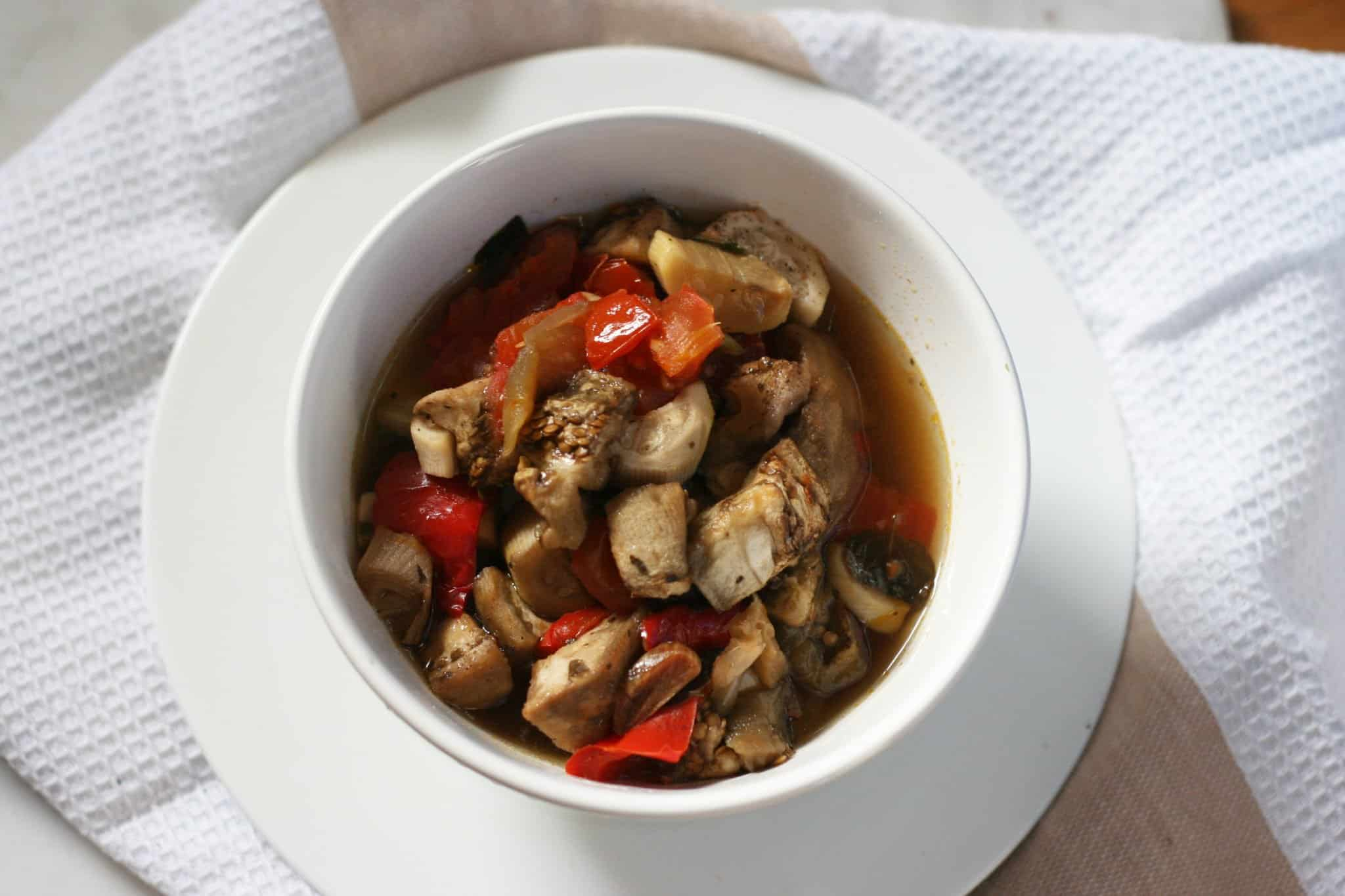 Slow cooker Mediterranean veggies served together in a white ceramic bowl on a large white linen