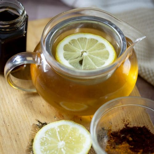 lemon ginger green tea in a tea cup with a lemon wedge