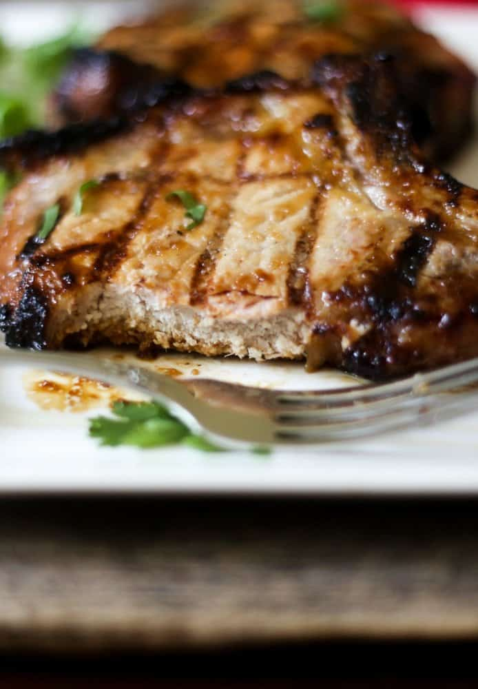 grilled teriyaki pork chops that have been sliced and ready to eat on a white plate
