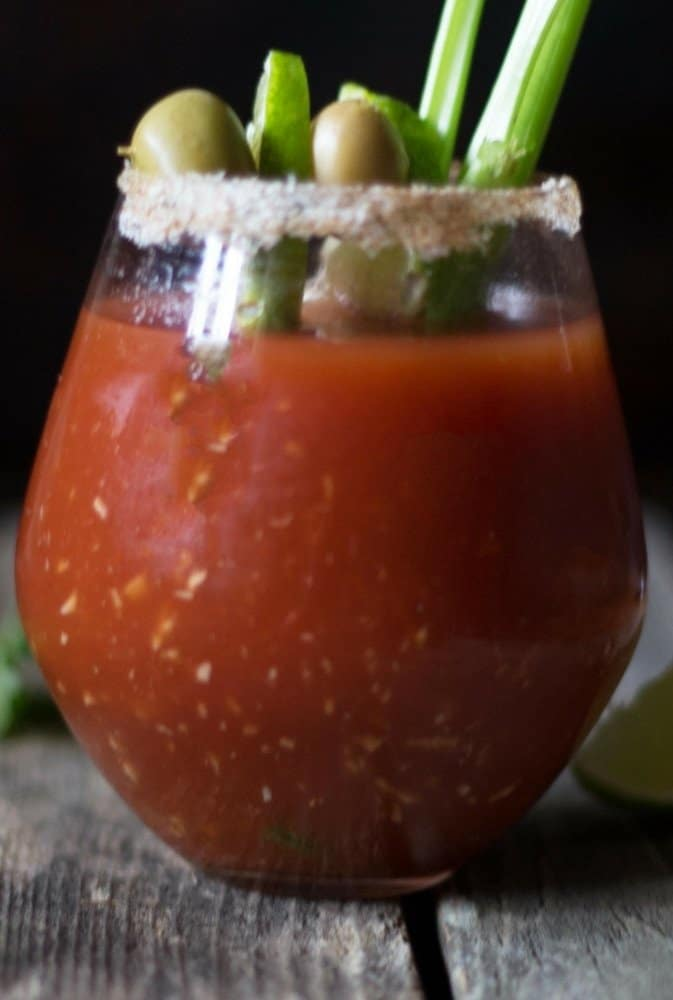 A clear glass filled with a delicious Bloody Mary with a celery stick and the glass is rimmed with salt, topped with olives and limes.