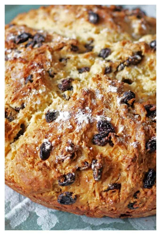 Irish Soda Bread filled with raisins on a green linen.