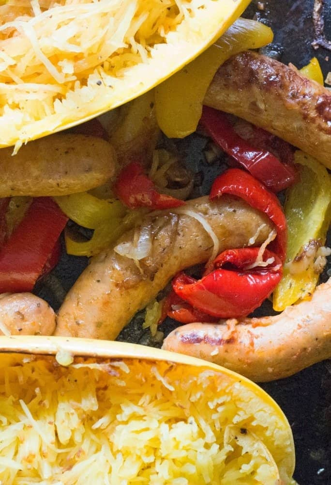 sheet pan chicken sausage with peppers and onions over spaghetti squash