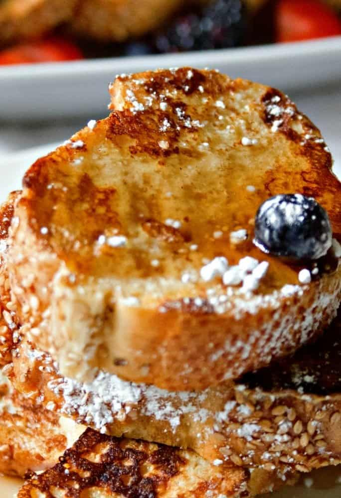 a side view of skinny french toast stacked on a while plate with fresh fruit and warm maple syrup sprinkled with confectioner sugar