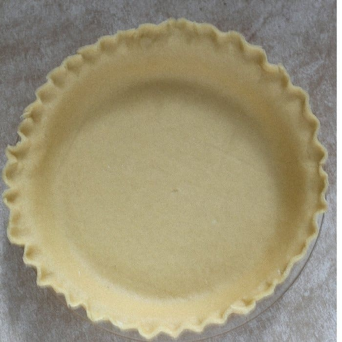 An aerial view of a buttery flaky pie crust with crimped edges ready to be either baked or filled with a filling.