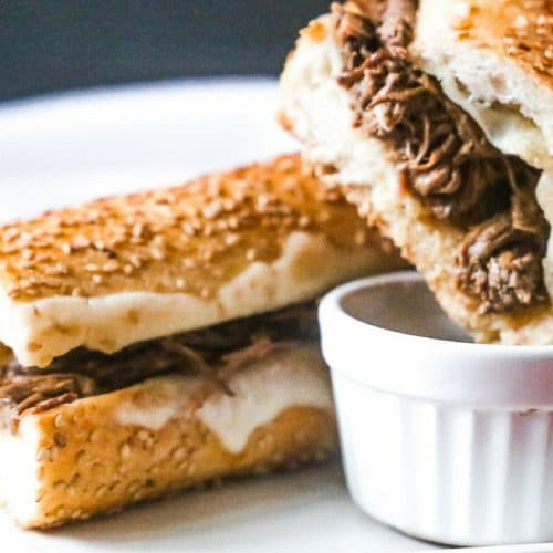 warm slow cooker french dip sandwich with melted provolone cheese dipped into a au jus sauce