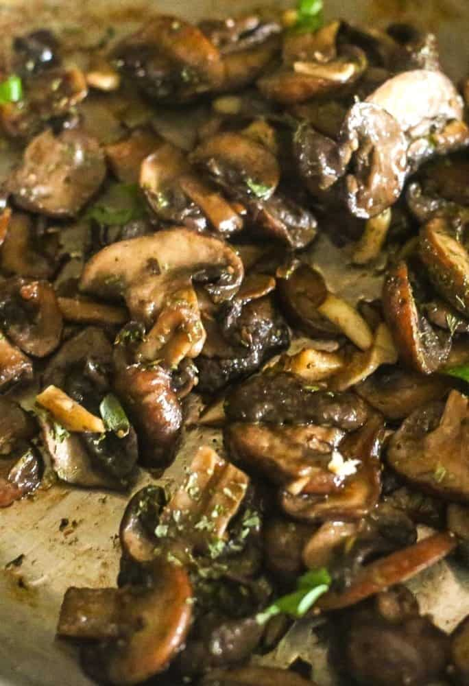 A side view of sliced sauteed mushrooms cooked with white wine, butter and garlic in a silver saute pan.