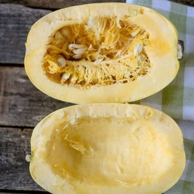 An aerial view of healthy butternut squash cut in half on a wooden surface with a green and white checkerboard linen to its side, one side has seeds removed the top half is showing the spaghetti squash with the seeds.