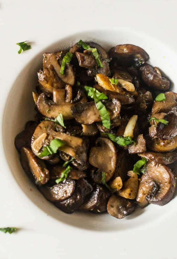 An aerial view of sauteed mushrooms cooked with garlic and white wine and sprinkled with fresh parsley in a white bowl