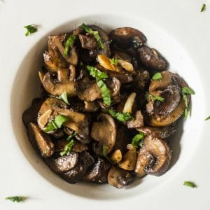 An aerial view of sliced sauteed mushrooms with garlic and wine with chopped parsley in a small white bowl