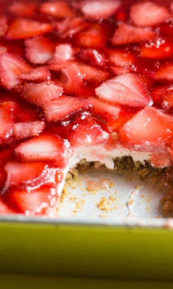 A side view of the best strawberry pretzel dessert recipe with slice cut showing the bottom pretzel layer then the yummy cream cheese layer and topped with the strawberry layer/