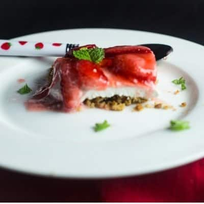 A side view of a delicious slice pf strawberry pretzel pie that shows the three layers ona white dessert plate.of delicious pretzel salad on a white dessert plate with fresh mint sprinkled around the plate.