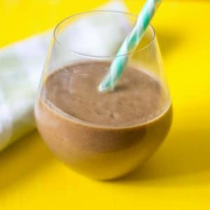 A side view of a chocolate protein smoothie with a green and white straw with a yellow backdrop.