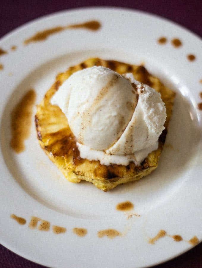 Grilled pineapple topped with a big scoop of fresh vanilla ice cream with rum sauce sprinkled around the white plate.