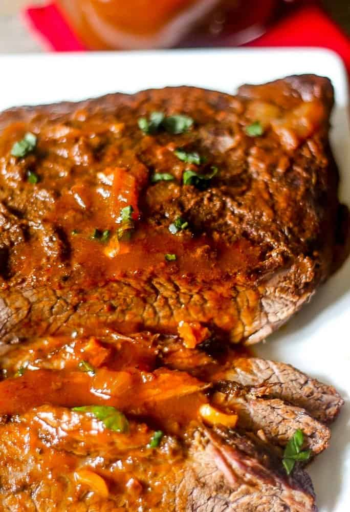 A tasty beef brisket cooked in an Instant Pot and topped with a delicious homemade chipotle barbecue sauce on a large white platter.