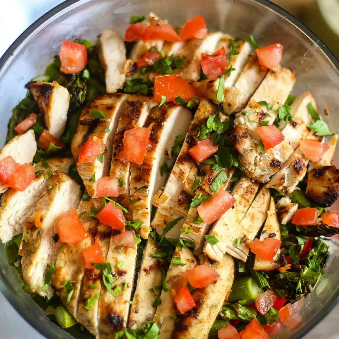 Layered grilled chicken asparagus salad in a large glass bowl topped with vine ripe tomatoes and chopped parsley.