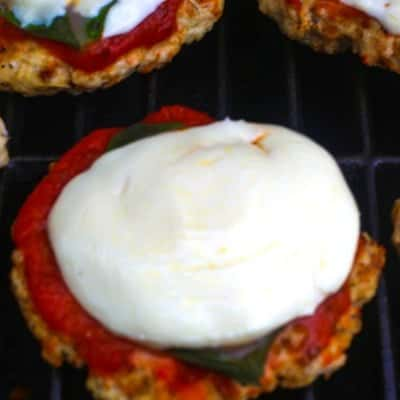Chicken parmesan burger being grilled with marinara sauce, fresh basil leaves, and mozzarella.