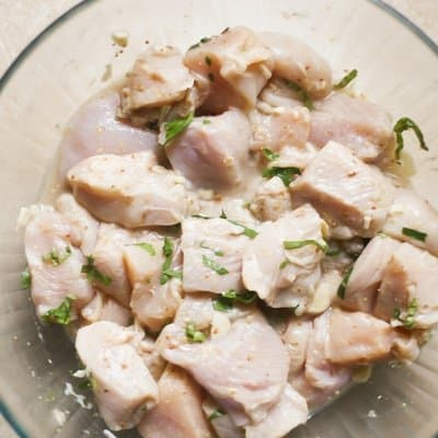 overhead picture of chicken cubes in a citrus marinade for chicken in a glass bowl