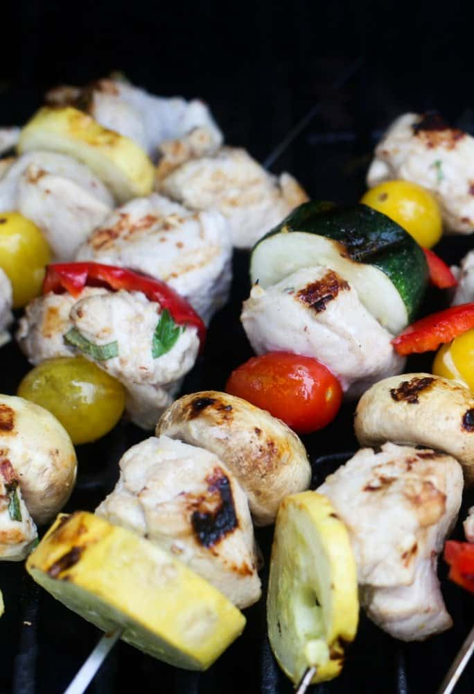grilled chicken citrus kebobs with veggies on silver steel skewers grilling on a gas grill