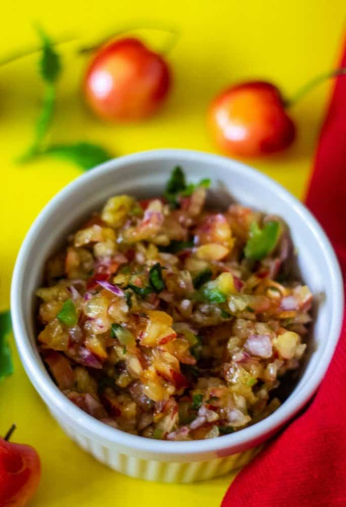 sweet and spicy cherry salsa made with Skylar Rae® cherries and jalapenos in a white bowl on a yellow background with a Red linen placed to the right of the salsa bowl.