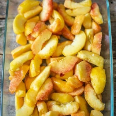 fresh peaches that have been peeled and quartered in a rectangle glass baking pan ready for a crumble topping to be baked to make peach crumble.