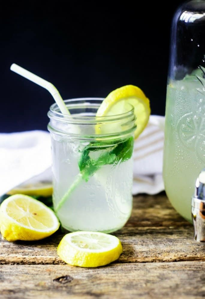 Thirst quenching ginger lemonade with mint and a lemon wedge on a wooden table ready to be served!