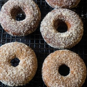 Four baked apple cider donuts with a cinnamon sugar topping on a black mesh rack.