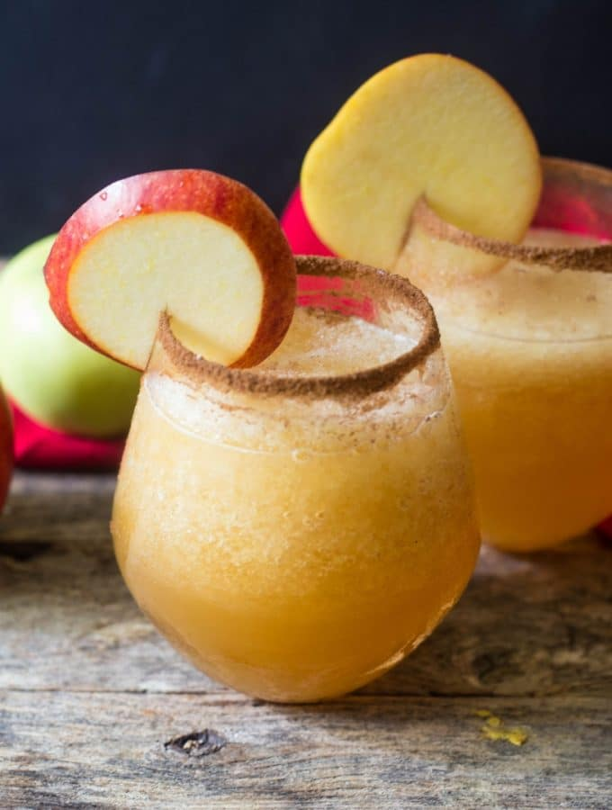 Two glasses of caramel apple vodka slush with the glasses rimmed with cinnamon sugar for garnish on a wooden table with apples a a red linen on the table.