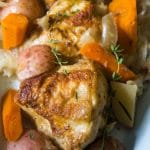 Hard cider braised chicken cabbage potatoes, fennel, apples, carrots on a platter.
