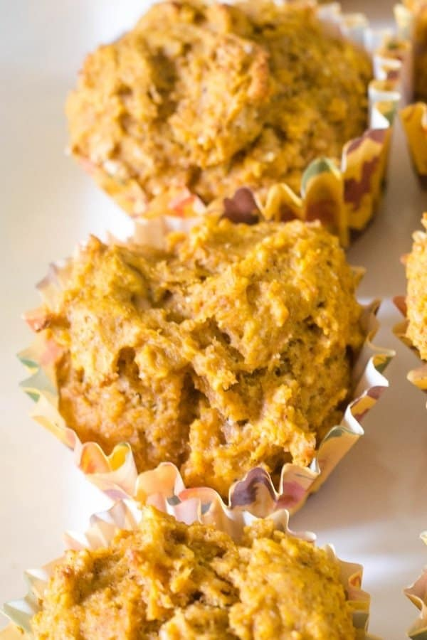 Healthy Pumpkin Muffins in autumn cupcake liners on a white dessert platter.