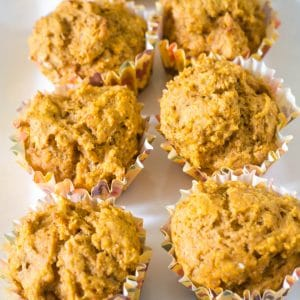 Easy pumpkin muffins in fall muffin liners on a white plate.