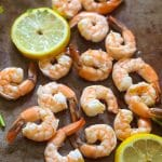 the easiest poached shrimp on a large brown platter with lemon wedges