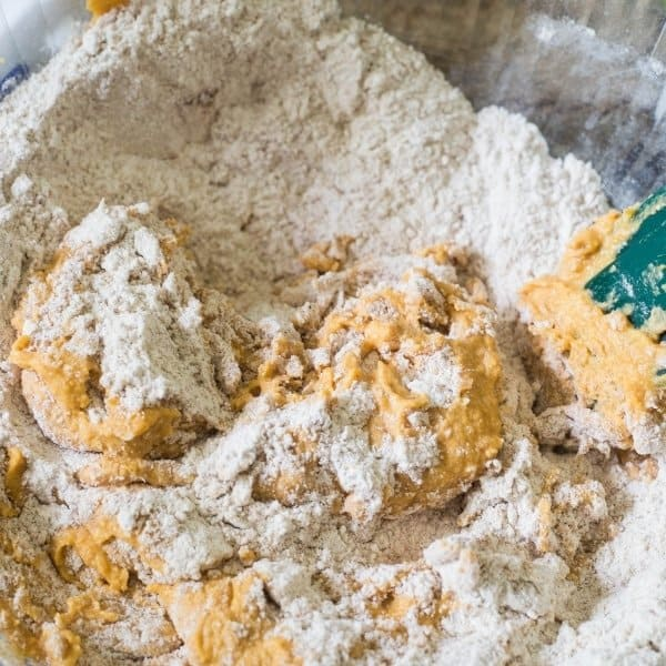 Flour mixture and pumpkin puree mix being folded together with a green spatula in a glass mixing bowl to make healthy pumpkin muffins.