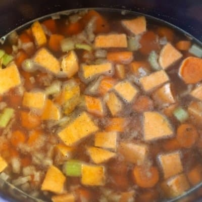 chopped carrots and veggies in vegetable broth simmering to make carrot coconut soup