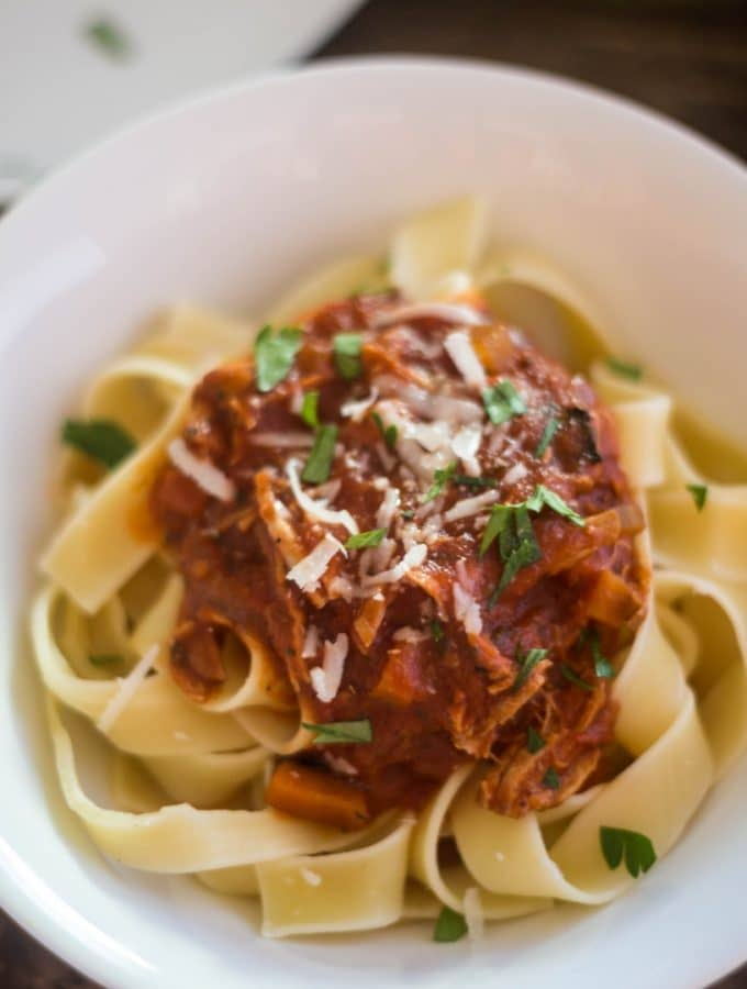 Hearty Pork ragu over pappardelle pasta sprinkled with fresh parsley and fresh grated parmesan reggiano in a white pasta bowl.