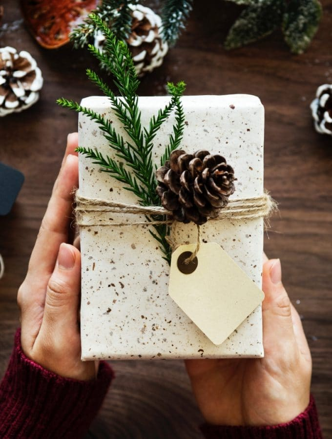 A gift wrapped with pretty white paper,a ribbon, green pine,and a pinecone.
