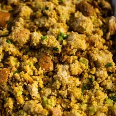 Cornbread, veggies, and herbs in a large white casserole dish to be baked to make Southern Cornbread Dressing.