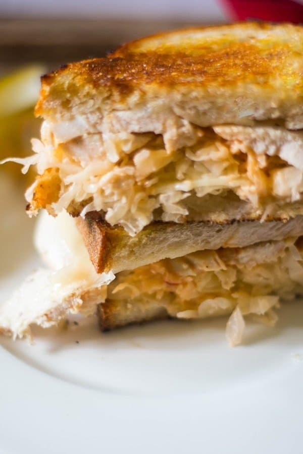 A grilled turkey reuben sandwich that has been grilled and sliced in half with melted Swiss cheese, Russian dressing and sauerkraut on a white plate with pickles.