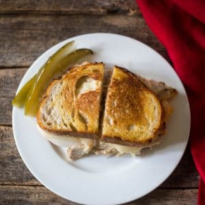 A delicious grilled golden brown crispy reuben sandwich with melted swiss cheese, Russian dressing, sauerkraut on a white plate with pickles.