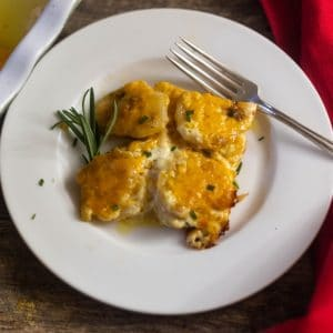 Easy Cheesy Scalloped Potatoes garnished with fresh rosemary on a white plate