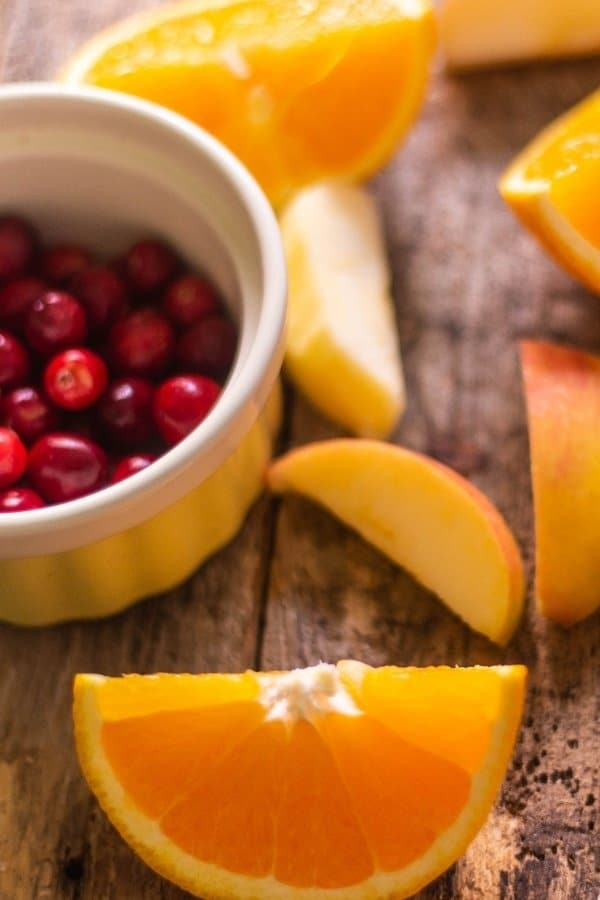 Sliced oranges and apples and a bowl of cranberries on a small yellow bowl, ingredients for cranberry orange relish!