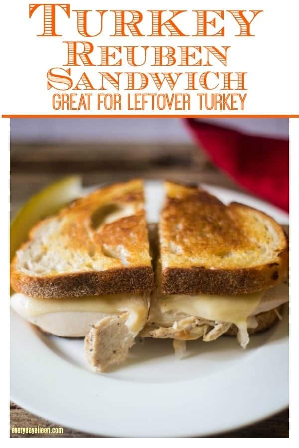 A delicious turkey reuben sandwich with leftover roasted turkey, melted swiss cheese, sauerkraut, Russian dressing, on toasted crispy rye bread.