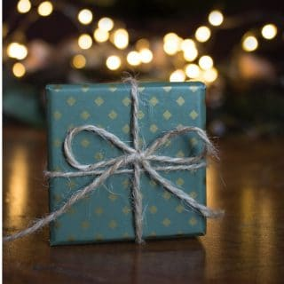 A present wrapped in pretty blue wrapping paper signifying unique kitchen gifts