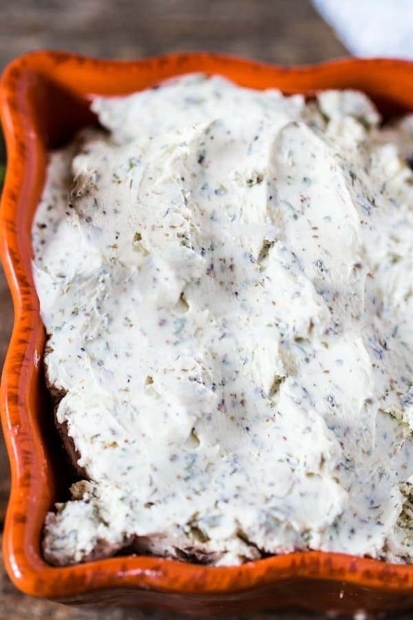 Homemade boursin cheese in an orange square ceramic bowl.