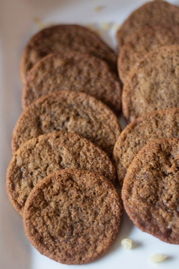 Crispy Gingersnap cookies stacked on a white platter.