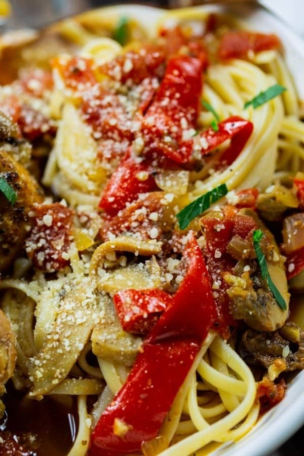 Delicious chicken cacciatore with sauteed peppers, mushrooms, and black olives over pasta.