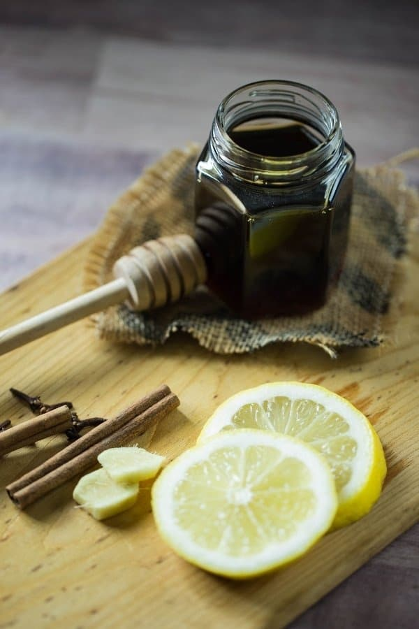 A small jar of honey, lemon wedges, whole cloves, and cinnamon on a wooden plank.